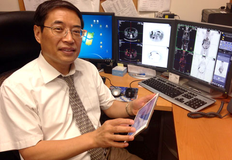 Dr. Frank Liu holds up his iPad at his office desk, demonstrating how he now has access to multiple screens.